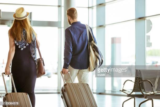 rear view of couple walking together in airport - izusek imagens e fotografias de stock