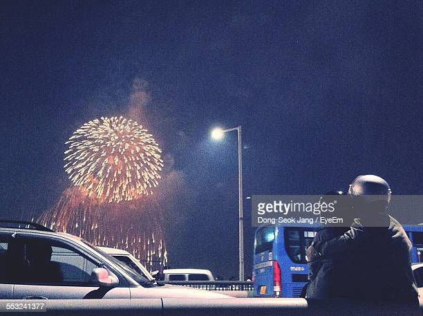 Rear View Of Couple Watching Fireworks Display From Bridge At Night