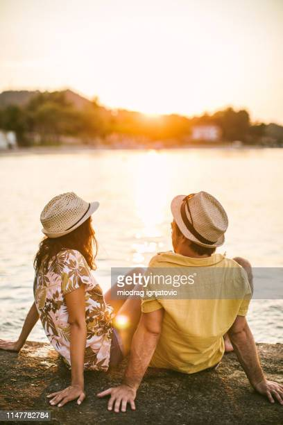 rear view of couple watching sunset - hot love stock pictures, royalty-free photos & images