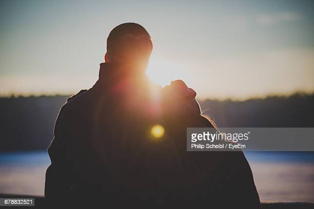 Rear View Of Couple Watching Sunset