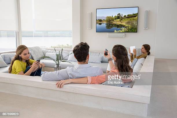 Rear view of couple watching television with their daughters busy in different activities
