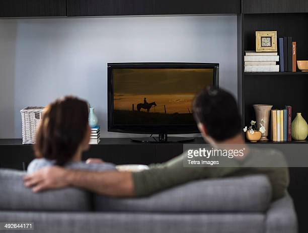 Rear view of couple watching tv, Jersey City, New Jersey, USA