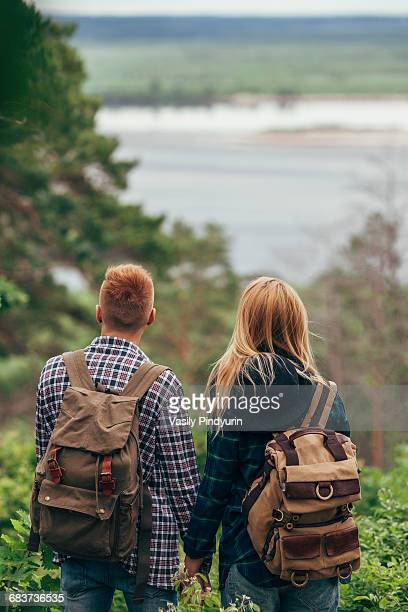 Rear view of couple wearing backpack standing in forest