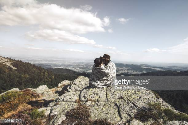 rear view of couple wearing hats kissing on mountain against sky - avvolto in una coperta foto e immagini stock