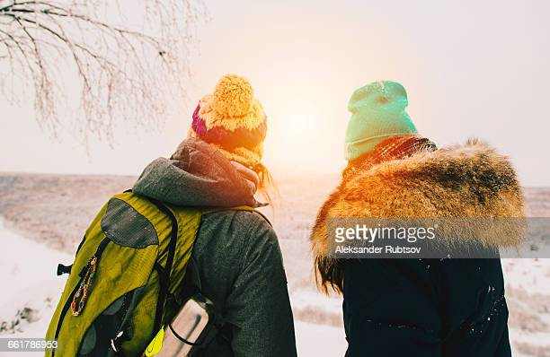 rear view of couple wearing knit hats looking away at view - 毛皮の飾り ストックフォトと画像