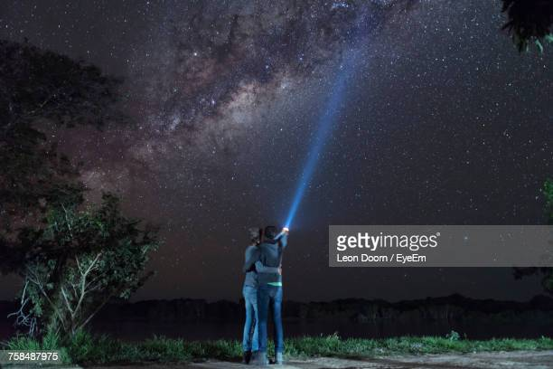 Rear View Of Couple With Arm Around Lightning Torch Against Sky At Night