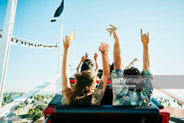rear view of couple with arms raised about to begin descent on roller coaster in amusement park - opwinding stockfoto's en -beelden