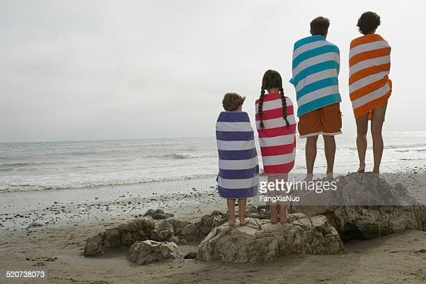 rear view of couple with two children wrapped in towels - wrapped in a towel stock pictures, royalty-free photos & images