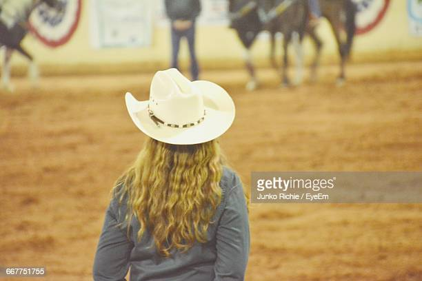 Rear View Of Cowgirl Standing On Field