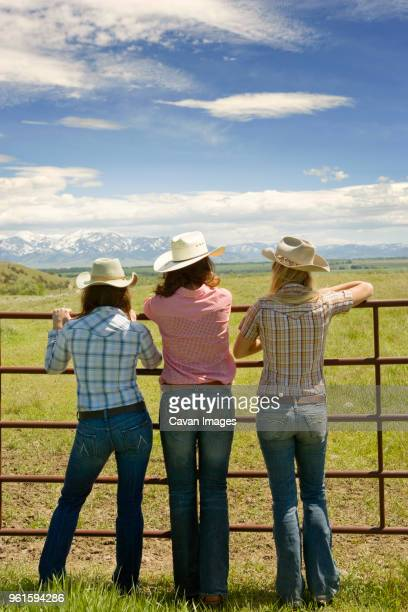 rear view of cowgirls standing by gate against sky - cowgirl photos et images de collection