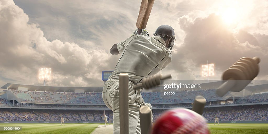 Rear View Of Cricket Ball Hitting Stumps Behind Batsman : Stock Photo