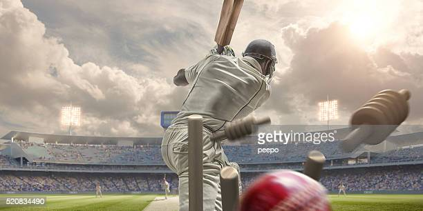rear view of cricket ball hitting stumps behind batsman - cricket stockfoto's en -beelden