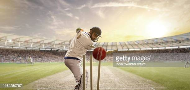 rear view of cricket ball hitting the stumps behind the batsman - batting stock pictures, royalty-free photos & images
