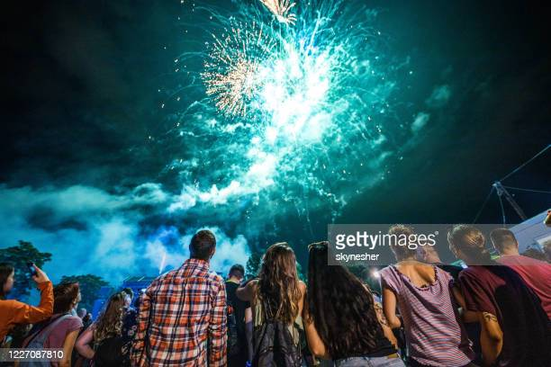 rear view of crowd of people watching fireworks at night. - fireworks stock pictures, royalty-free photos & images