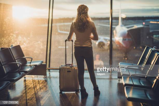 rear view of curly female at airport. - airport stock pictures, royalty-free photos & images