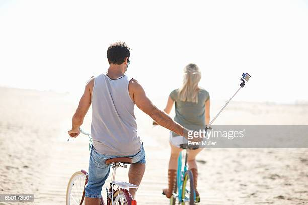 Rear view of cycling man taking a selfie at Venice Beach, Los Angeles, California, USA