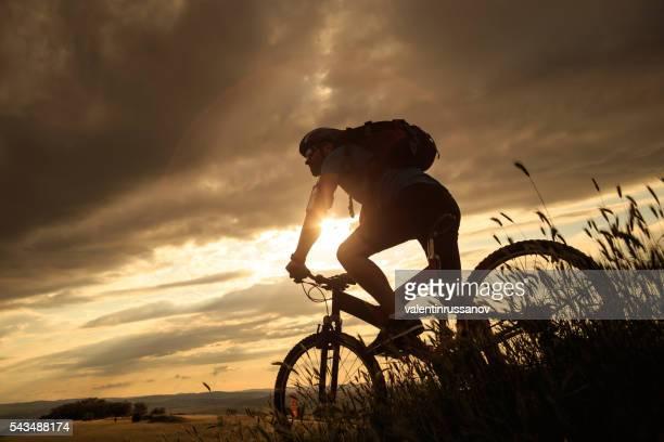 Vue arrière de cycliste Escalade jusqu'au sommet de la montagne