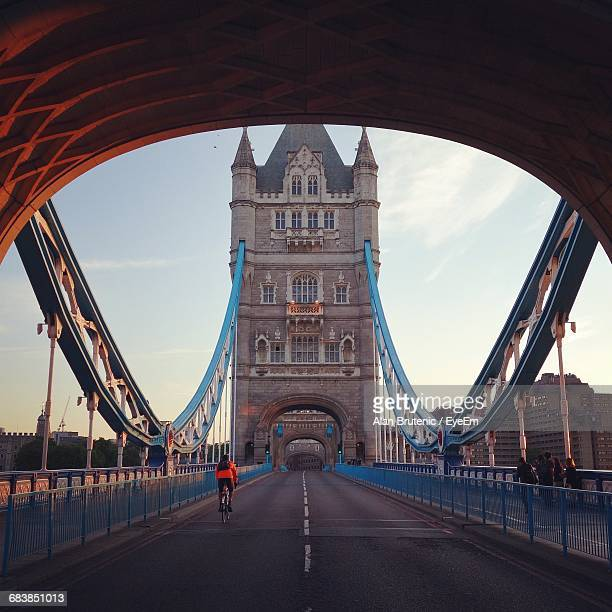 rear view of cyclist riding bicycle on tower bridge against sky at morning - international landmark stock pictures, royalty-free photos & images