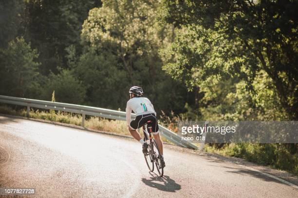 rear view of cyclist road cycling on a country road - road cycling stock pictures, royalty-free photos & images