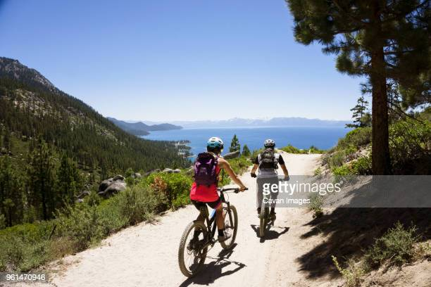 rear view of cyclists riding bicycles on dirt road against clear blue sky - lake tahoe stock pictures, royalty-free photos & images