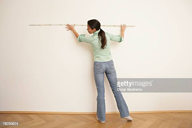 rear view of dark haired woman measuring wall with folding rule