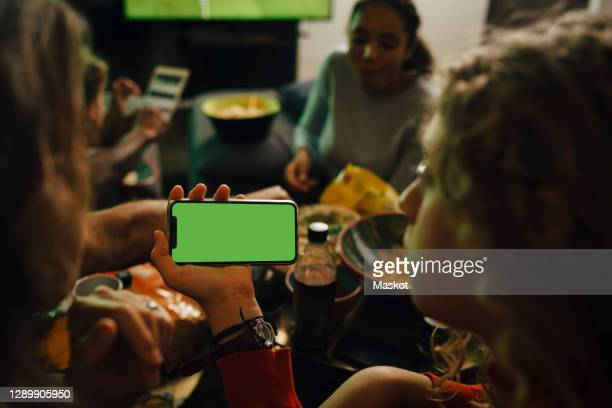 rear view of daughter and mother looking at smart phone during sporting event - watch what happens: live stock pictures, royalty-free photos & images