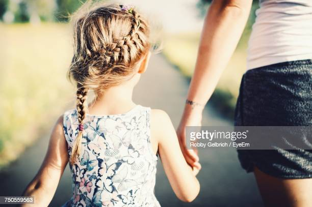 Rear View Of Daughter Holding Hand Of Mother