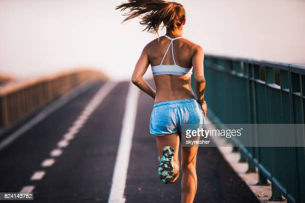 rear view of determined female athlete jogging on the street. - sports bra stock pictures, royalty-free photos & images