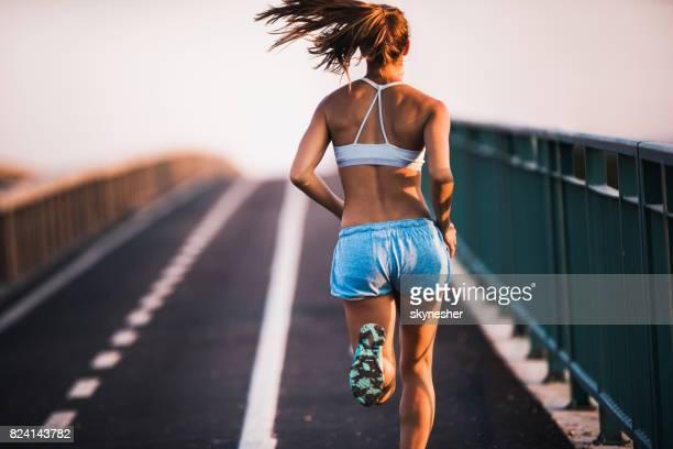 Vista posterior de determinado atleta femenina para correr en la calle.
