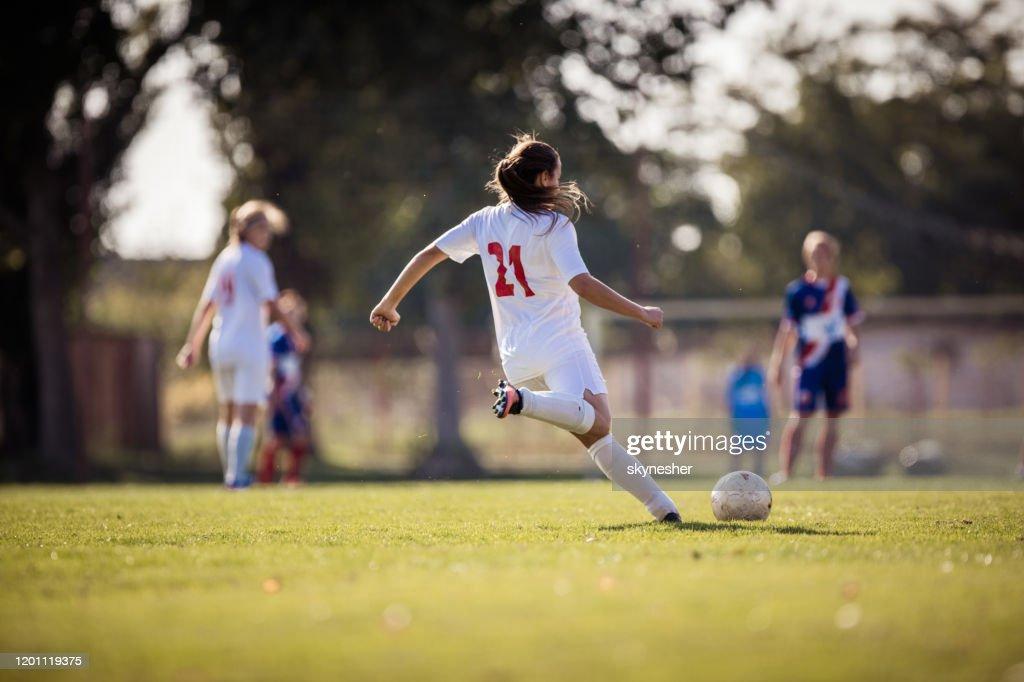 Visão traseira de determinada jogadora chutando a bola em uma partida. : Foto de stock