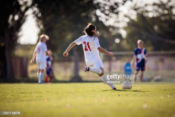 rear view of determined female soccer player kicking the ball on a match. - shooting at goal stock pictures, royalty-free photos & images