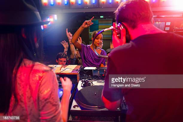 Rear view of disc jockey surrounded by people dancing