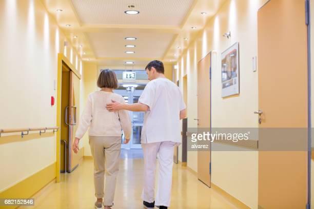 achteraanzicht van arts en vrouw lopen in gang - operatiekleding stockfoto's en -beelden