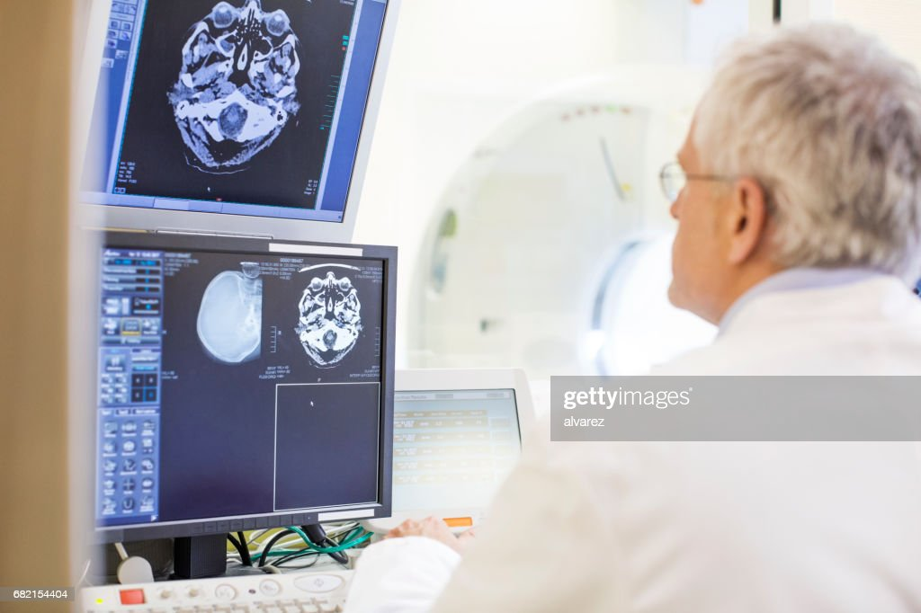 Rear view of doctor examining CAT scan reports : Stock Photo