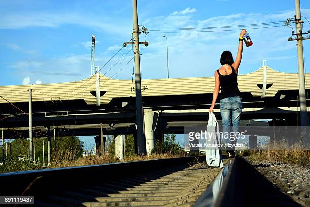 rear view of drunk woman walking on railroad track while holding liquor bottle - drunk woman stock pictures, royalty-free photos & images