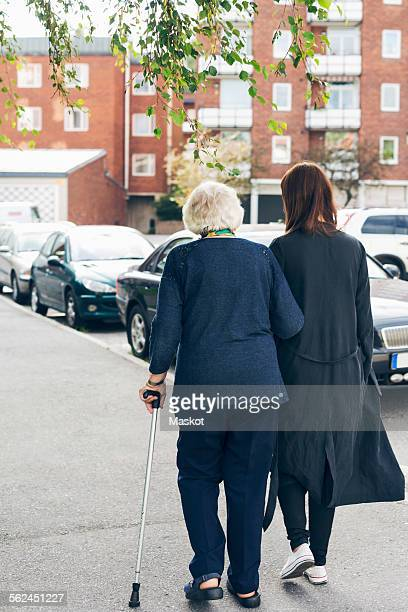 Rear view of elderly woman walking with granddaughter on sidewalk in city