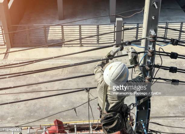 rear view of electrician repairing power lines - power occupation stock pictures, royalty-free photos & images