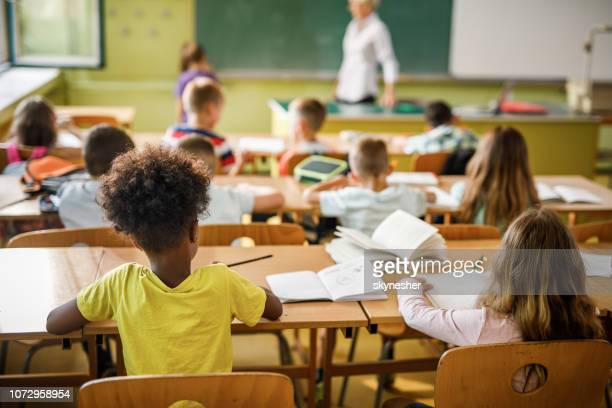 rear view of elementary students attending a class in the classroom. - school supplies stock pictures, royalty-free photos & images
