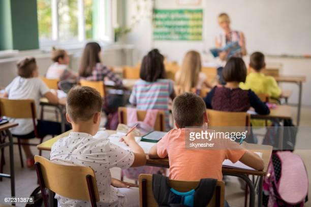 Rückansicht der Grundschüler im Klassenzimmer während der Vorlesung.