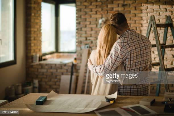 Rear view of embraced couple at construction site of their apartment.