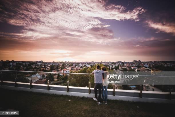Vista posterior de la pareja abrazado disfrutando en el hermoso amanecer en su terraza de ático.