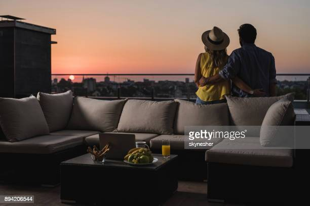 rear view of embraced couple looking at sunrise from a penthouse terrace. - balcony stock pictures, royalty-free photos & images