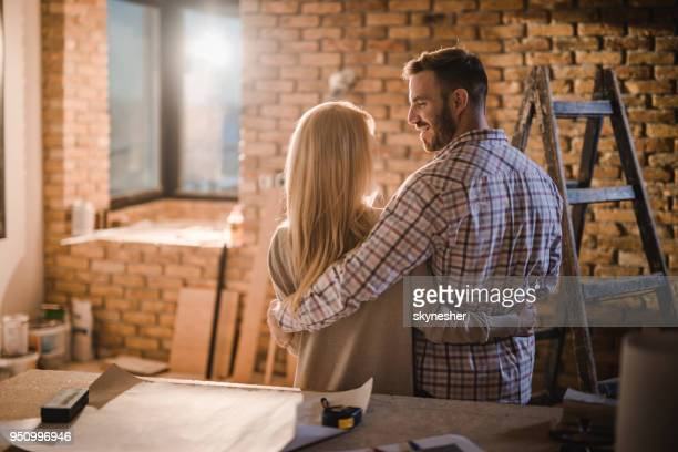 rear view of embraced couple talking at construction site of their apartment. - reform stock pictures, royalty-free photos & images
