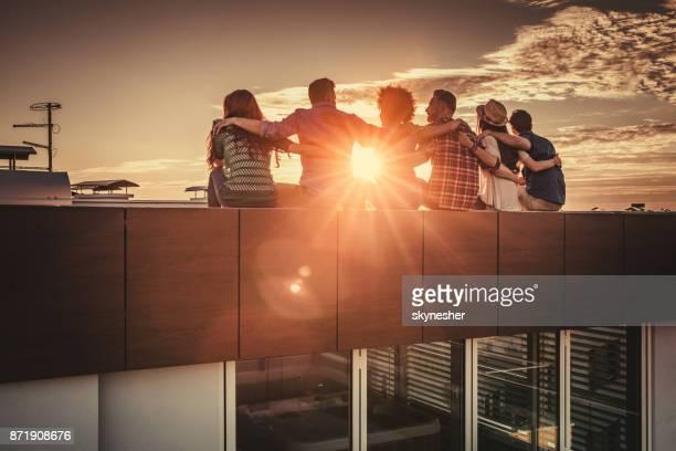 vista trasera de amigos abrazados relajantes en una terraza al atardecer. - amigos abrazados espaldas fotografías e imágenes de stock