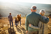 Rear view of embraced senior couple looking at their family in nature.