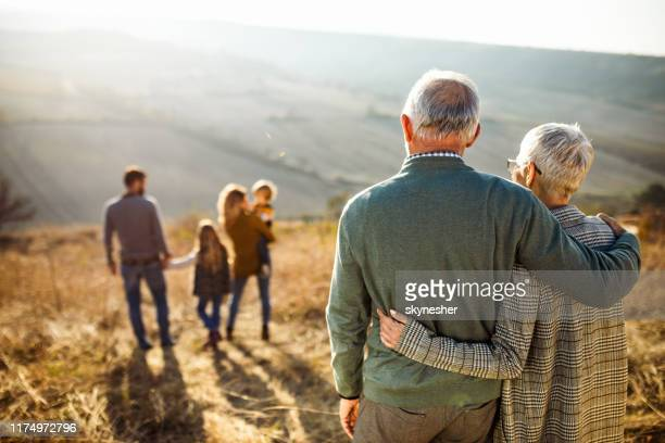 rear view of embraced senior couple looking at their family in nature. - family stock pictures, royalty-free photos & images
