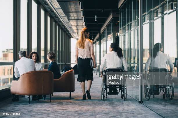 rear view of entrepreneur walking with disabled colleague while professionals discussing in background at workplace - differing abilities fotografías e imágenes de stock