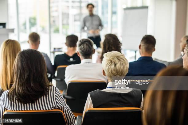 achteraanzicht van ondernemers die een business seminar bijwonen in de kamer van bestuur. - deelnemer stockfoto's en -beelden
