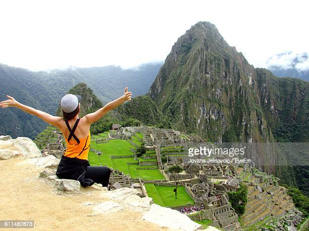 Rear View Of Excited Woman With Arms Outstretched Looking At Historic Machu Picchu