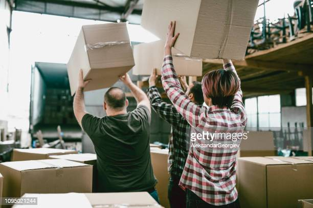 rear view of factory worker loading carton boxes for shipping - moving past stock pictures, royalty-free photos & images
